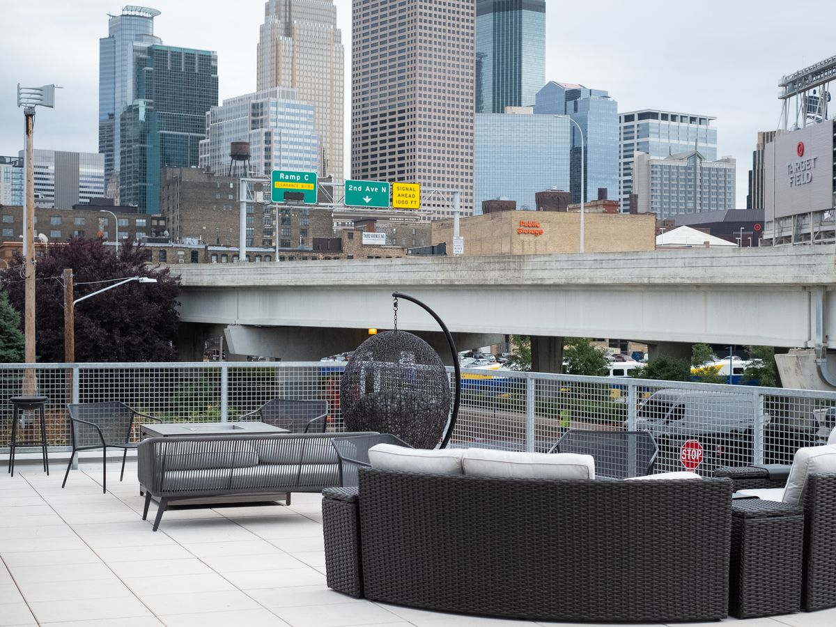 A large outdoor couch, hanging chair, and more seating on a rooftop patio that overlooks the downtown Minneapolis skyline