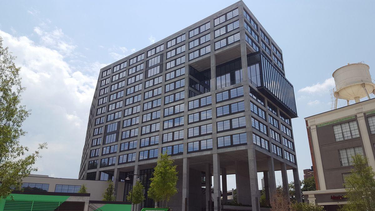 A concrete-framed, glassy office tower stands 12 stories over the Beltline and Kroger.
