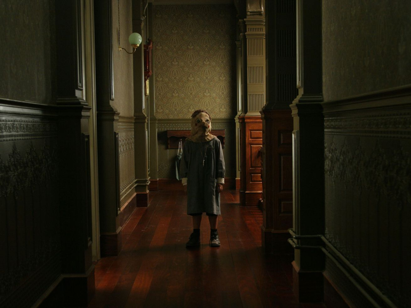 A child in a creepy mask stands in a dark hallway.