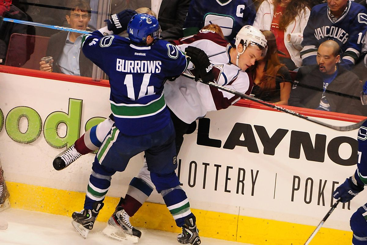Mar 28, 2012; Vancouver, British Columbia,CANADA; Vancouver Canucks forward Alexandre Burrows (14) checks Colorado Avalanche forward Jamie McGinn (11) during the first period at Rogers Arena. Mandatory Credit: Anne-Marie Sorvin-US PRESSWIRE