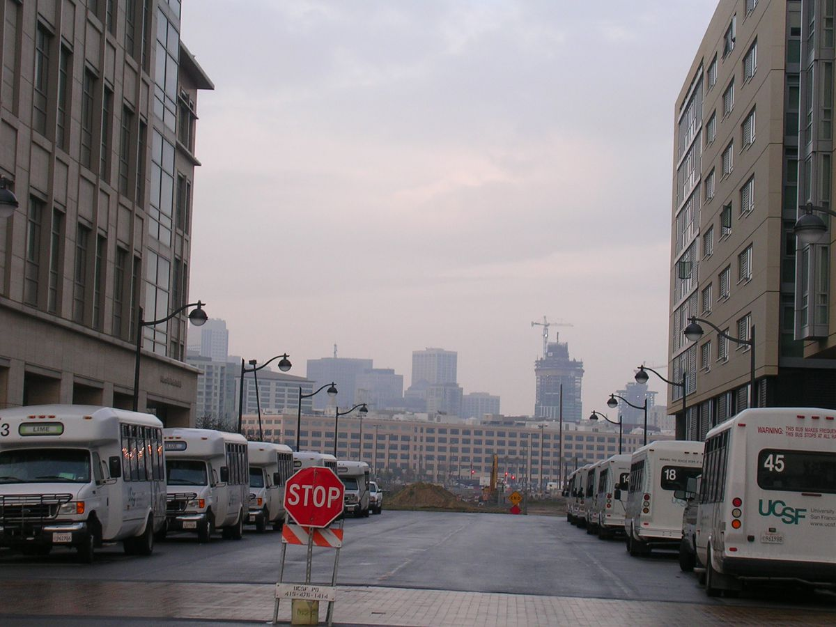 A street with rows of buses parked on each side. In the distance is a cityscape with various assorted buildings.