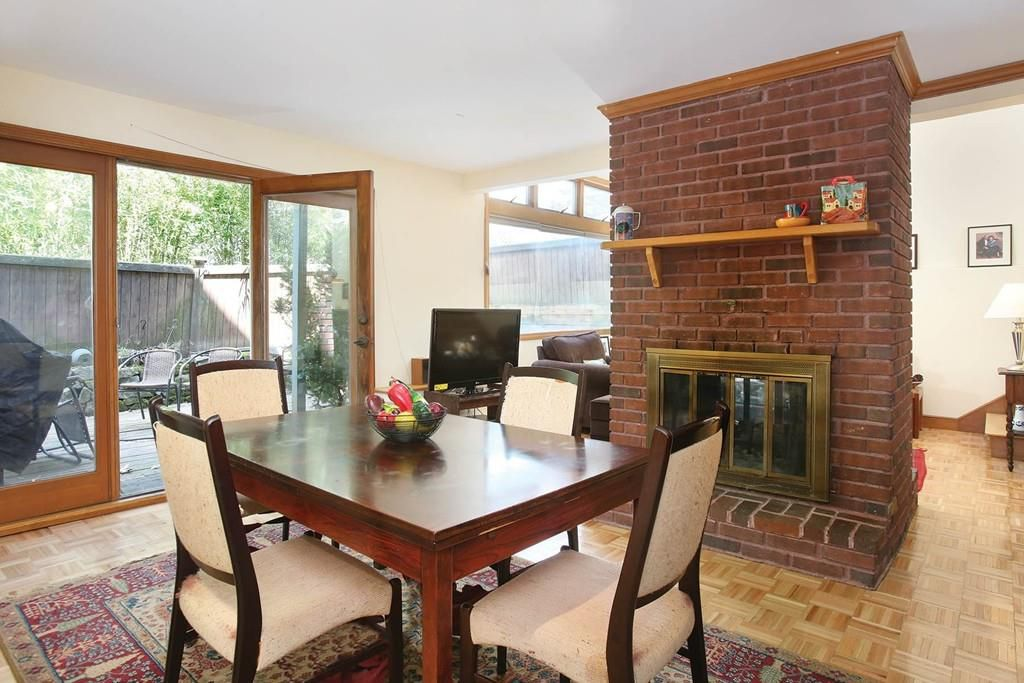 A dining room with chairs now on the other side of that column fireplace.
