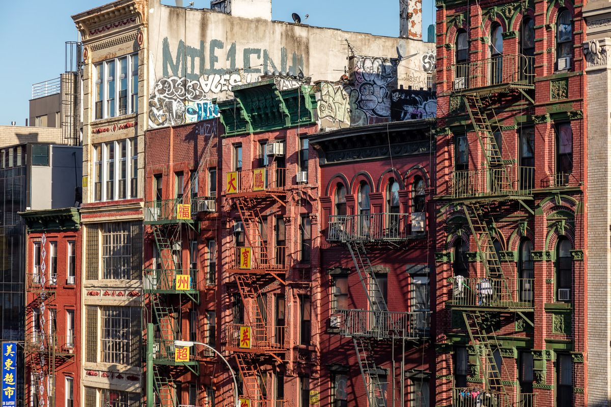 A row of red-brick apartment buildings on a street in Manhattan's Chinatown.