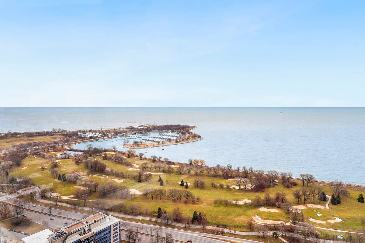 An elevated view of a golf course and harbor next to Lake Michigan.