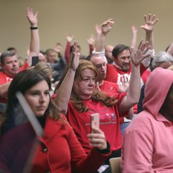 Audience members, many in Red for Ed shirts, raise their hands in support of a public commenter during a Tax Restructuring and Equalization Task Force meeting in the House Building on the state Capitol campus in Salt Lake City on Monday, Nov. 25, 2019.
