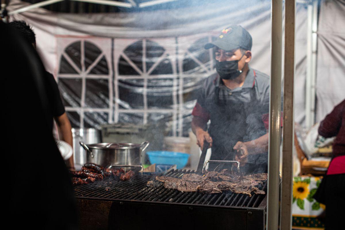 A masked vendor turns carne asada on a smoky grill.