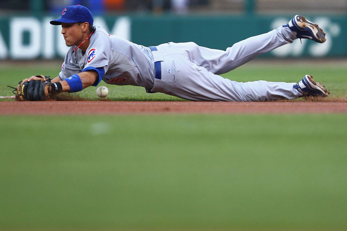 Darwin Barney of the Chicago Cubs attempts to field a line drive against the St. Louis Cardinals at Busch Stadium in St. Louis, Missouri.  (Photo by Dilip Vishwanat/Getty Images)