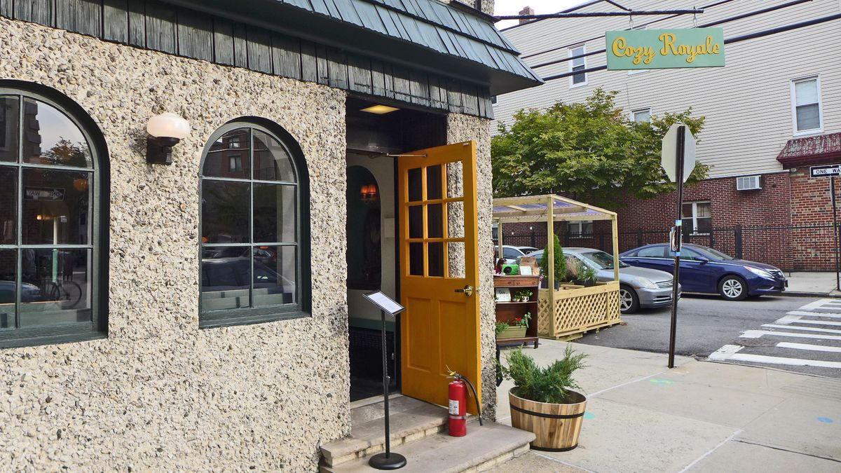 """The front of a corner restaurant with arched windows, a door that's propped open, and a baby blue sign that reads """"Cozy Royale"""""""