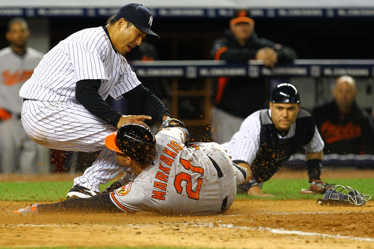 NEW YORK, NY - APRIL 30:  Hiroki Kuroda #18 of the New York Yankees tags out Nick Markakis #21 of the Baltimore Orioles who tried to steal home off of a wild pitch as Russell Martin #55 of the New York Yankees who flipped the ball to Hiroki looks on.