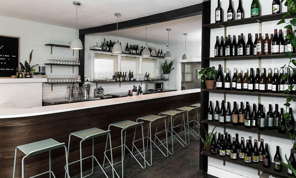 A wine bar stocked with bottles on open shelves, plus seating