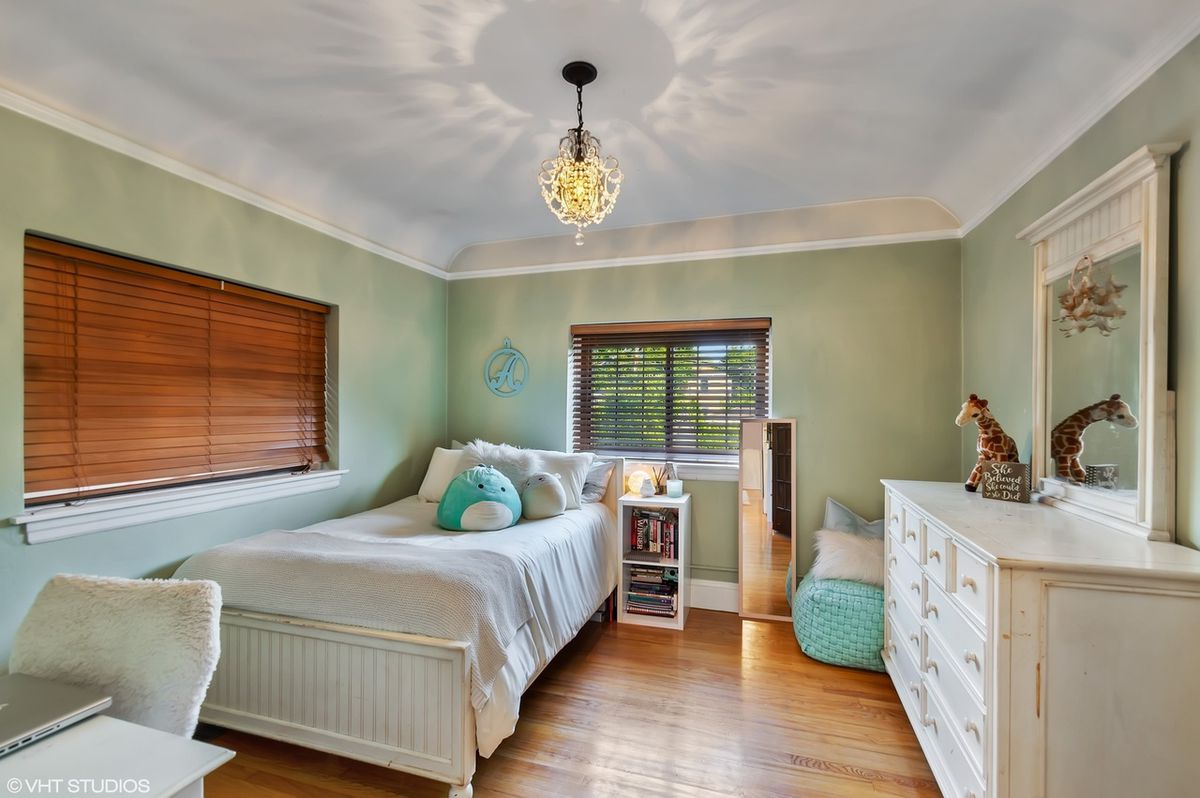 A children's bedroom with a single bed in the corner, a dresser, a desk, and light green walls.