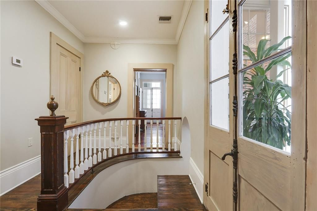 The top of a stairwell has white rails and a dark wood bannister leading to a hall with a window.