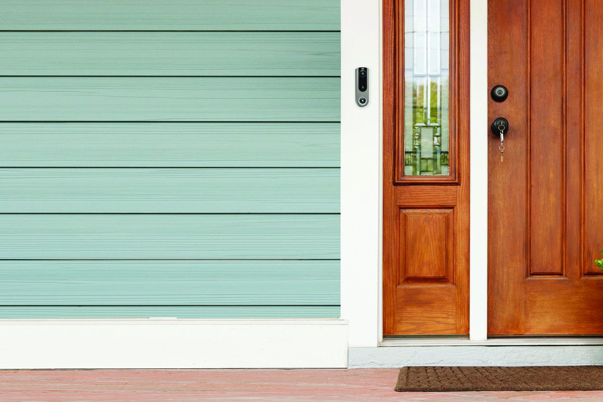 An ADT video doorbell to the left of a wooden front door on a blue house.