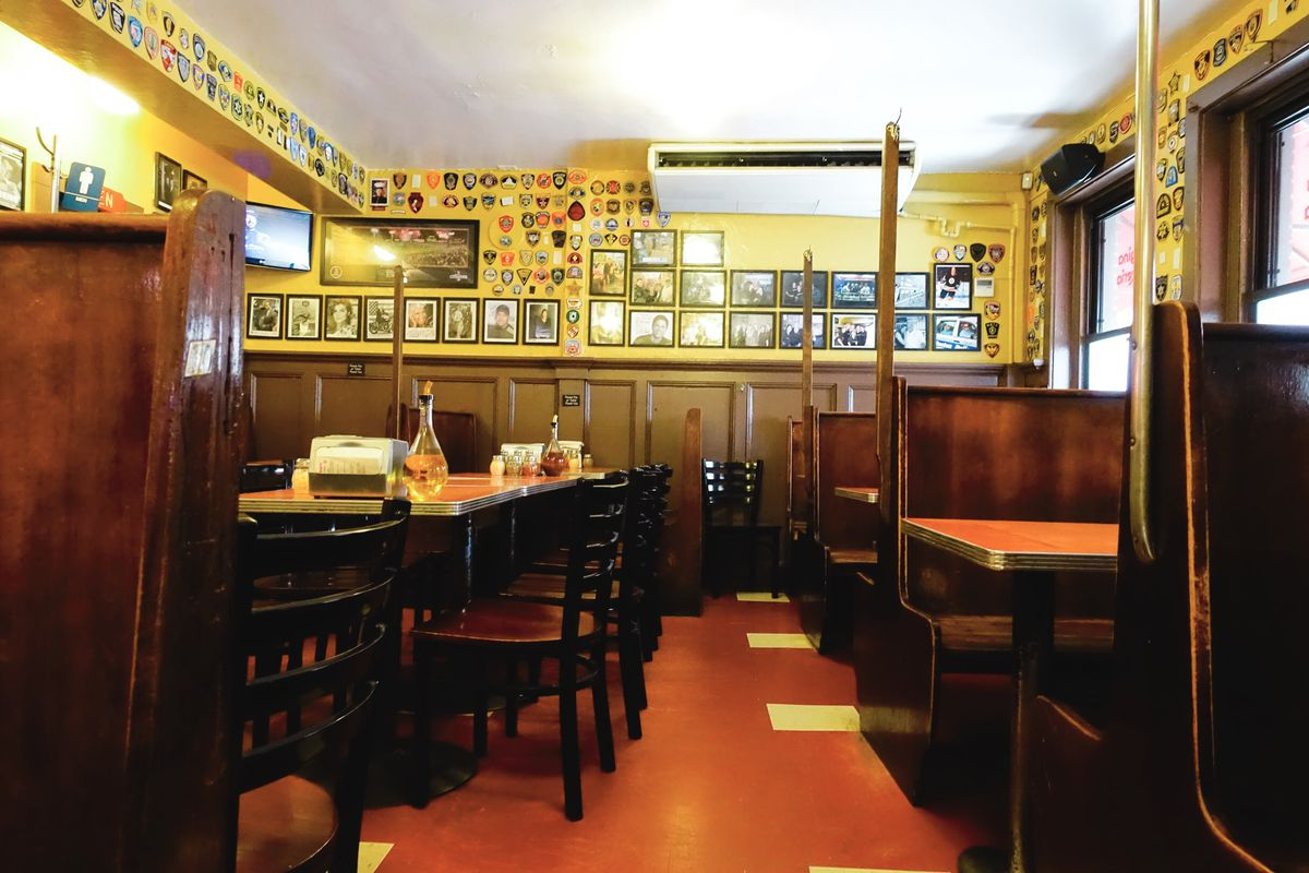 The dining room of Regina, featuring wood paneling, yellow walls plastered with photographs, some wooden booths, and other tables and chairs