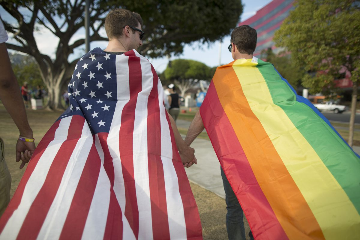 Two men hold hands while wearing the US flag and LGBTQ flag.