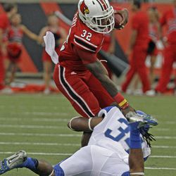 Louisville running back Senorise Perry (32) is stopped by Kentucky linebacker Kory Brown (34) on a run in an NCAA college football game at Cardinal Stadium in Louisville, Ky., Sunday, Sept. 2, 2012.