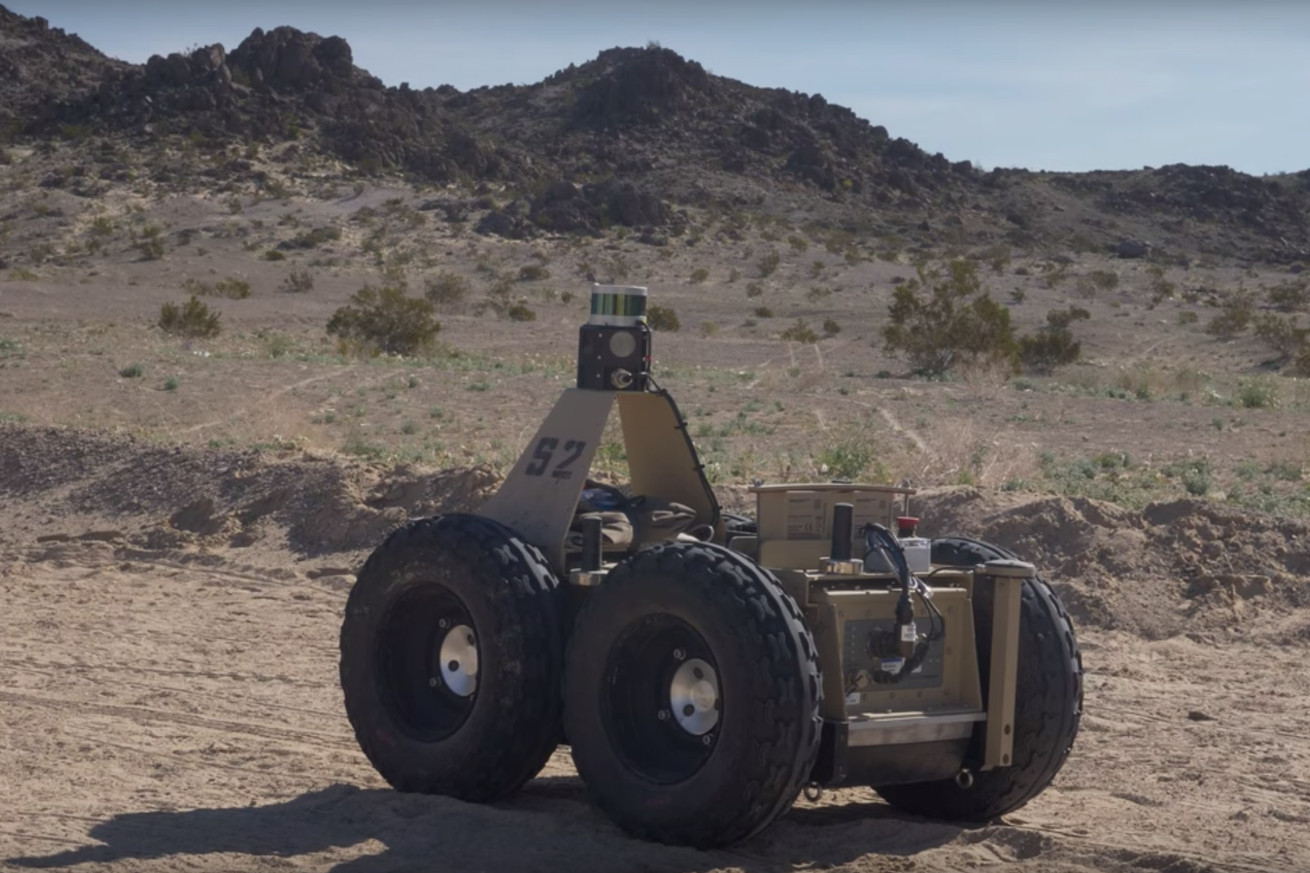 A small, tan, wheeled robot with giant wheels in the desert.