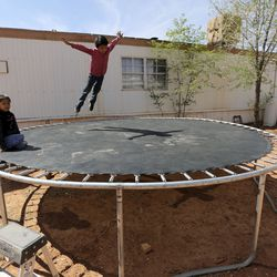 Sophie Hunt and Jarett Hunt play on a trampoline outside of their house in Halchita, San Juan County, which is part of the Navajo Nation, on Friday, April 17, 2020. The Navajo Nation has one of the highest per capita COVID-19 infection rates in the country. Sophie and Jarett got tested earlier in the day.