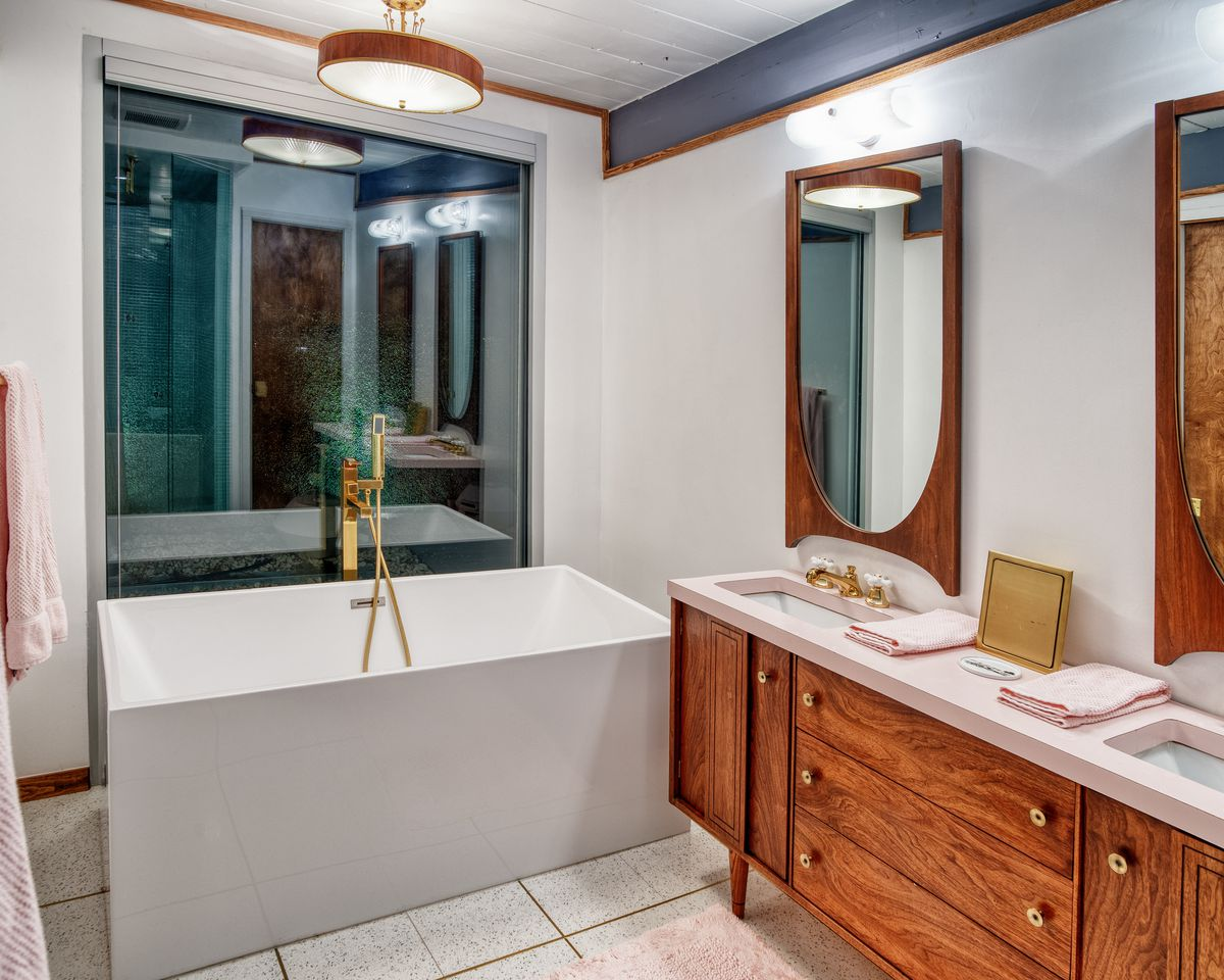 A bathroom in a midcentury modern home. There is a large bathtub, a sink, wooden cabinetry, mirrors, and a large window.  The walls are painted white.