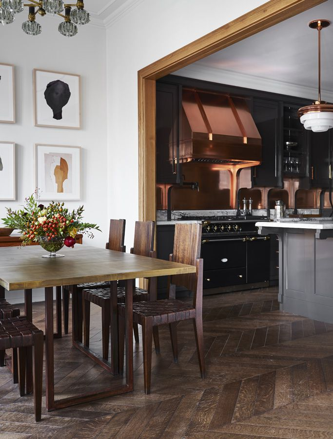 Looking from the dining area into the kitchen, where there's copper backsplashes and a copper range hood.