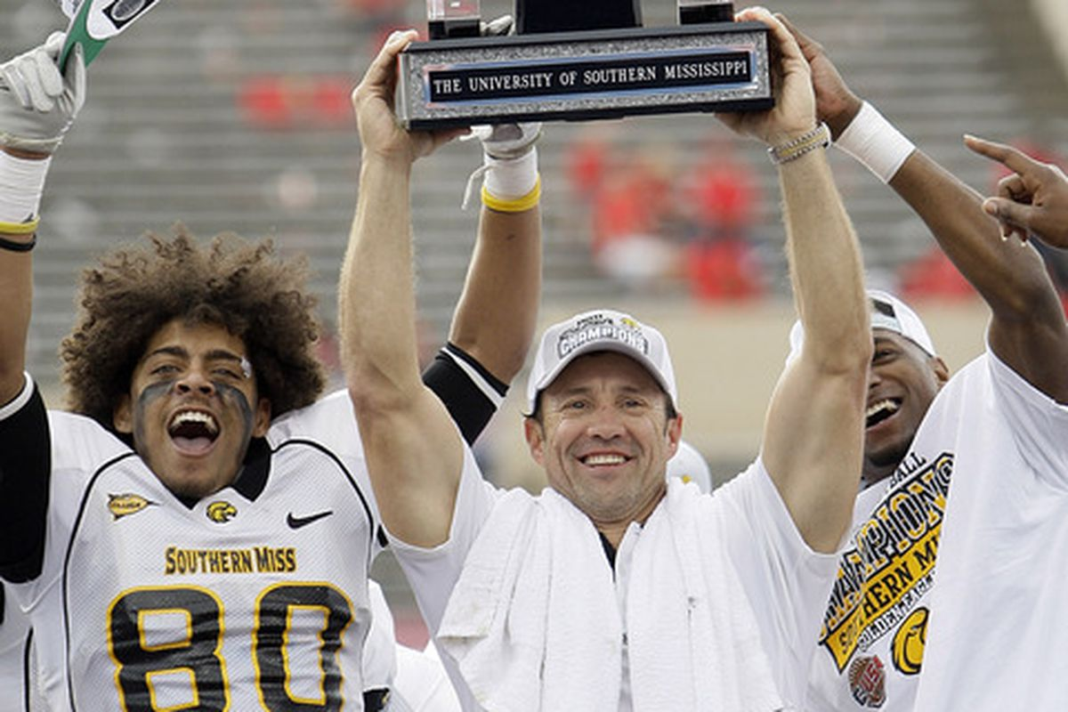 Head coach Larry Fedora of the Southern Miss Golden Eagles holds up the Conference USA trophy with Ryan Balentine #80 and Tim Green #43 after defeating the Houston Cougars 49-28 at Robertson Stadium on December 3, 2011.