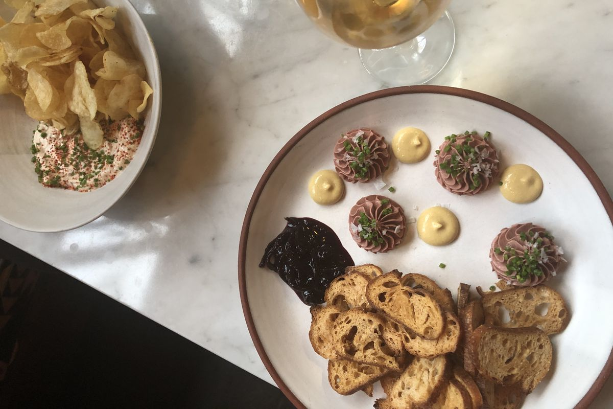 An overhead shot of two happy hour plates and two glasses of wine at Oui Wine Bar + Restaurant at SE Wine Collective