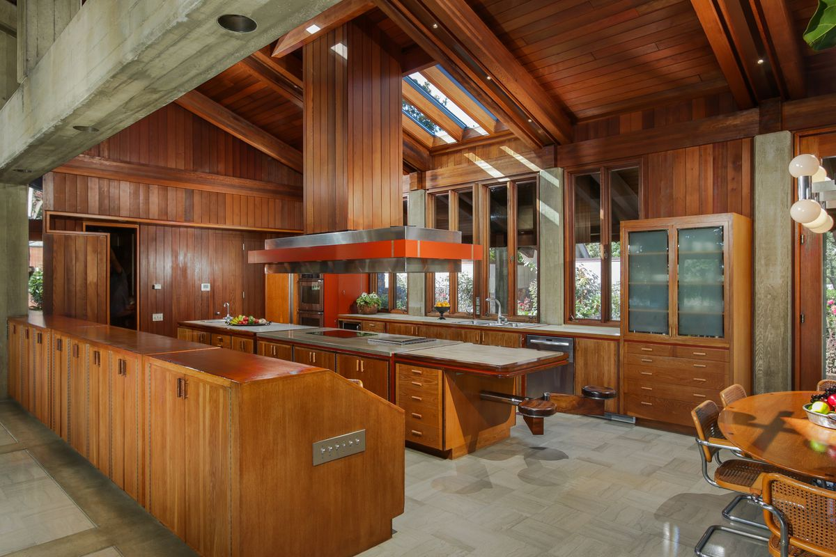 A spacious kitchen features wood cabinets, a large center island, and marble floors.