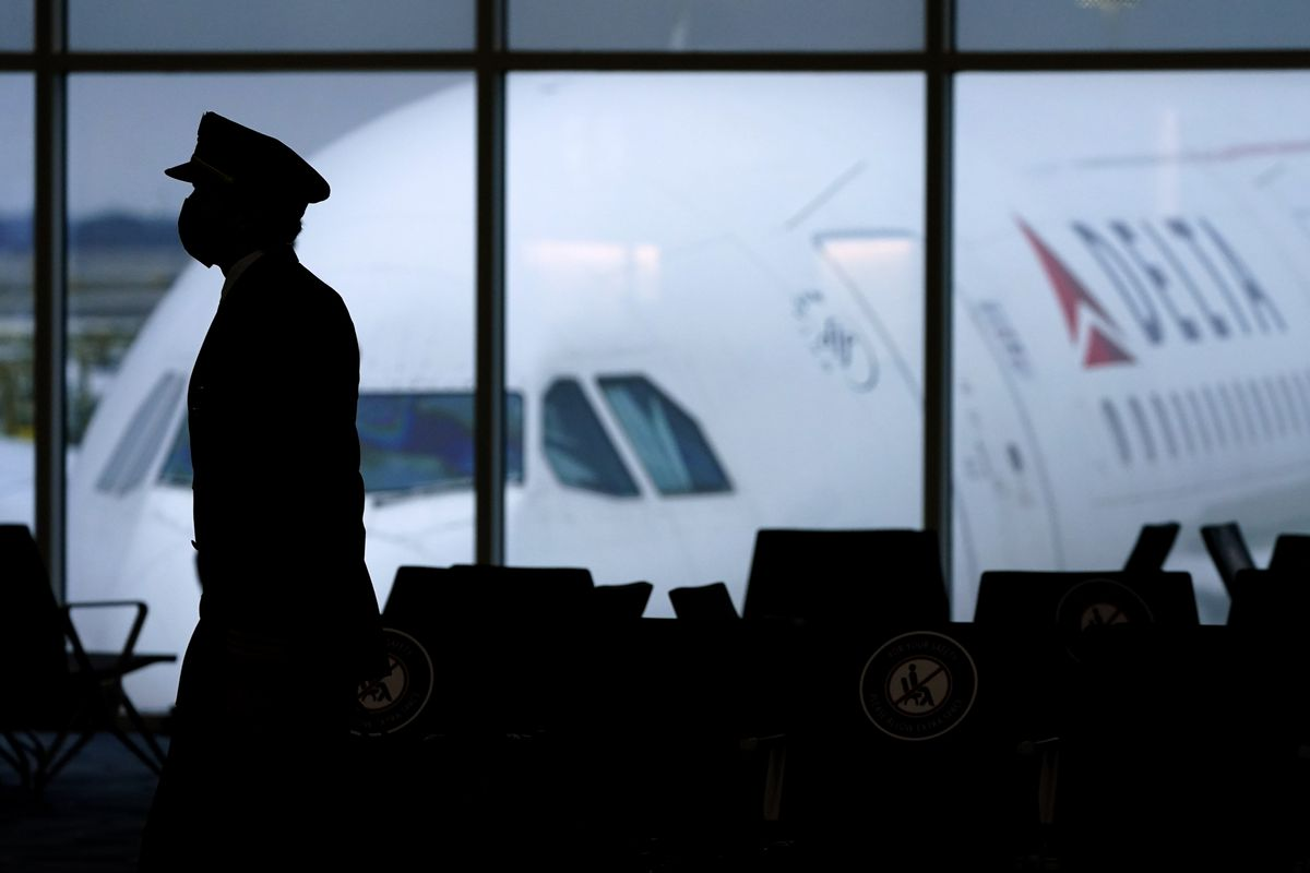 A Delta Airlines pilot wears a face mask as he walks through a terminal at Hartsfield-Jackson International Airport.