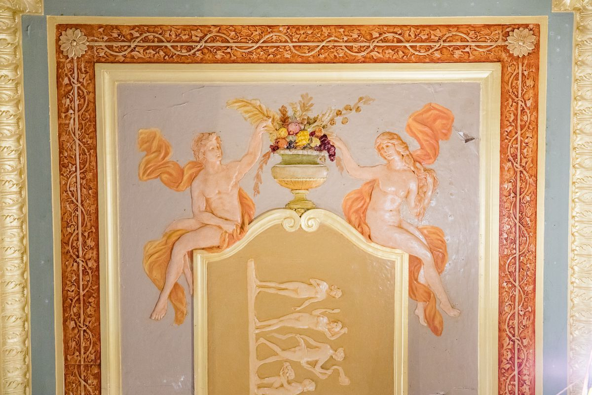 A ceiling panel with two naked figures, a man and a woman, reaching for a vase of flowers.  There are flower frames around the picture.