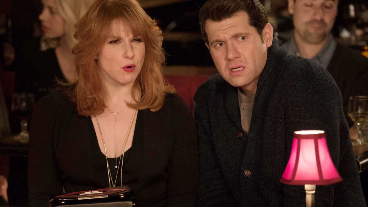 Julie Klausner and Billy Eichner scowling at a table