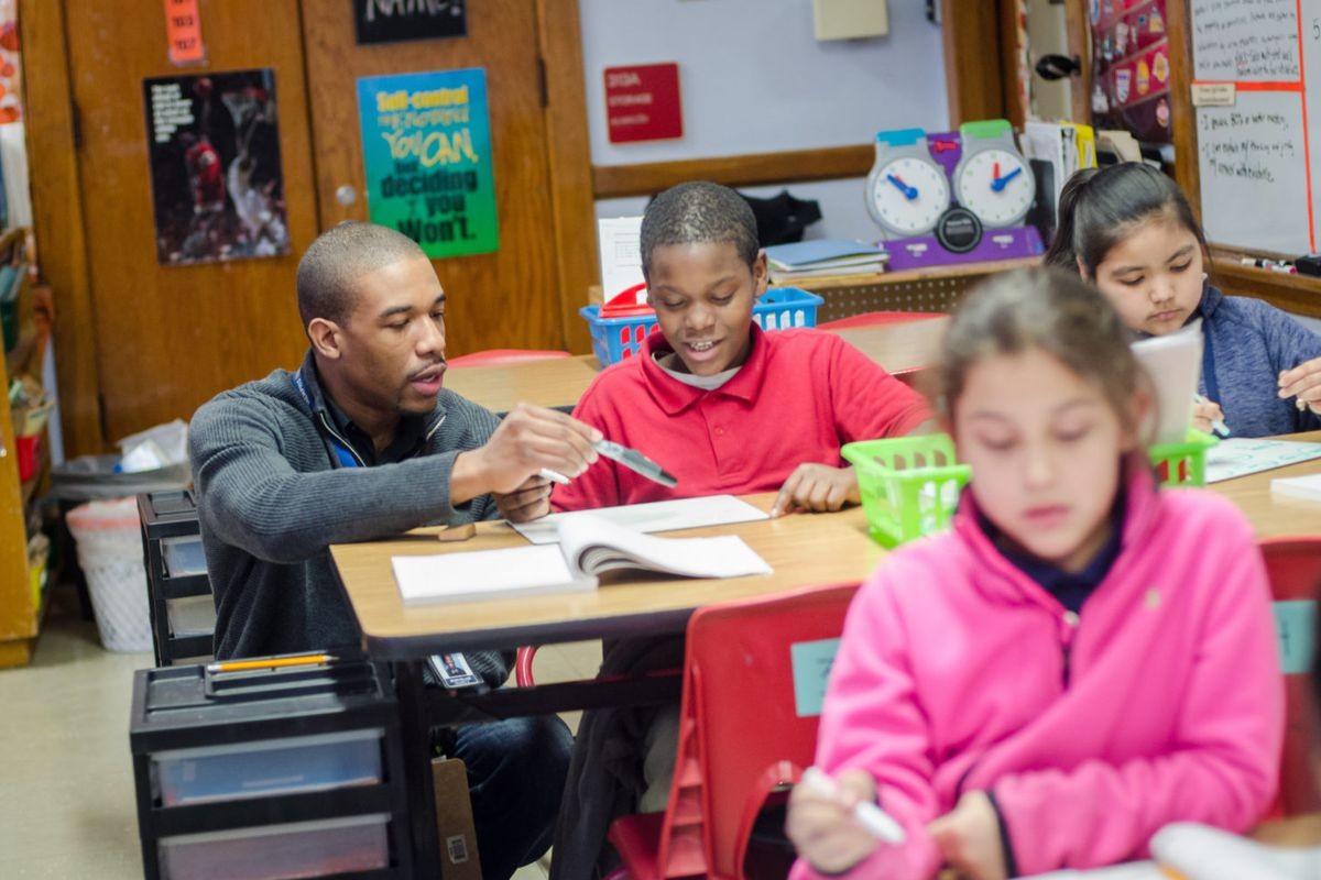 Treadwell Elementary math teacher Neven Holland, a graduate of the Memphis Teacher Residency program, helps his fourth-grade student with a problem.