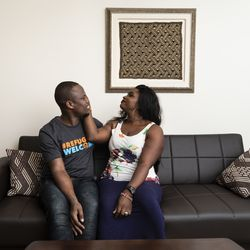 Celestine Mugisha and his wife, Winniefred Akello, embrace on the couch in their apartment in Rogers Park on the North Side, Jan. 30, 2020. Mugisha and Akello were married in Uganda in September 2016 and, days later, Mugisha moved to Chicago as part of the United States' refugee resettlement program. More than three years later, Akello was also resettled through the program and the couple was reunited at O'Hare International Airport on Jan. 22, 2020.