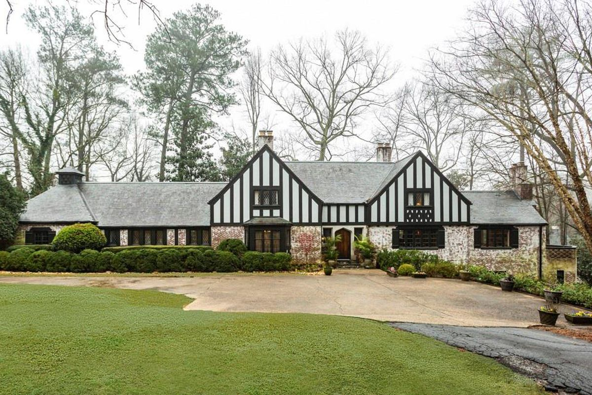 A huge Tudor home with a lot of trees around it on a large lot.