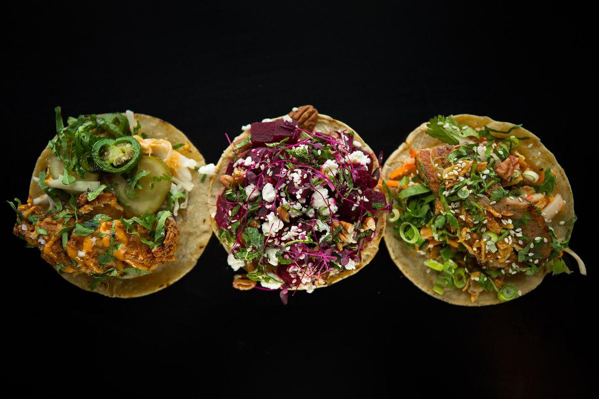 Three tacos on a black background from Breddos Tacos Soho