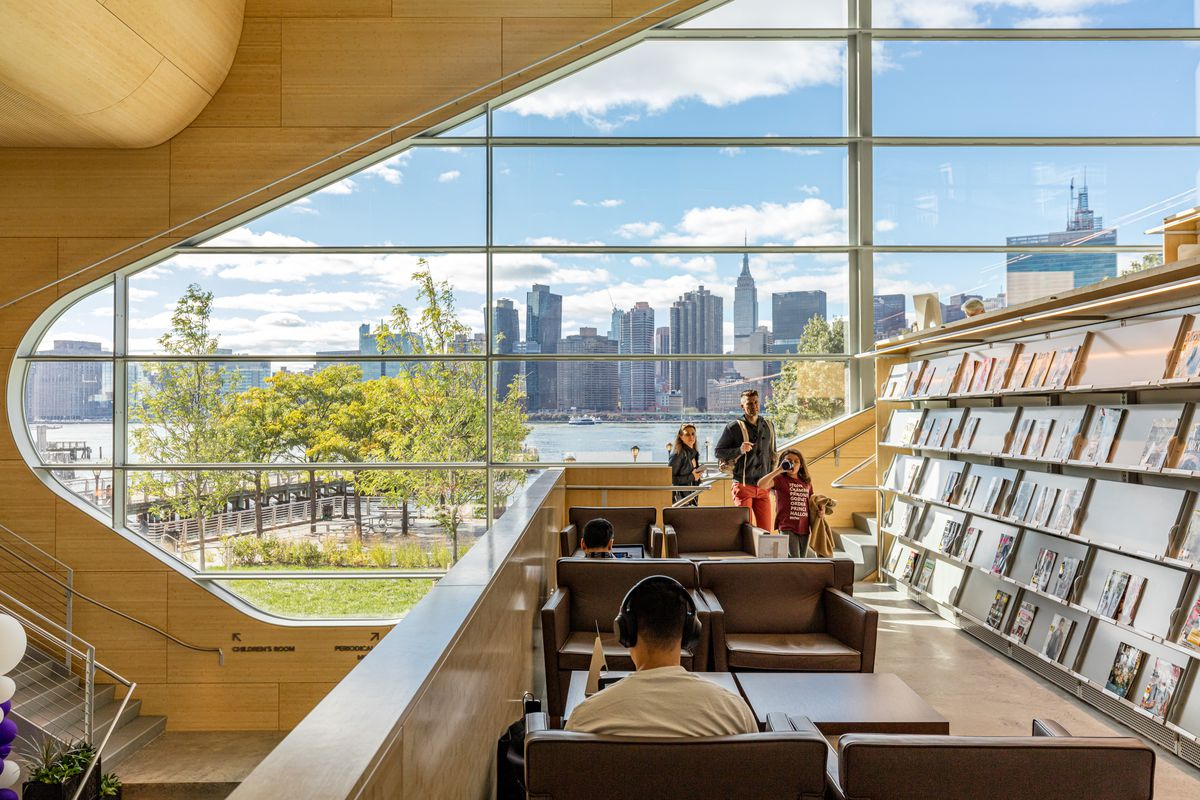 View of Manhattan's skyline out of a curved window at the Hunters Point library. The wall is a light wood, there are stacks filled with books, and seats with tables for studying.