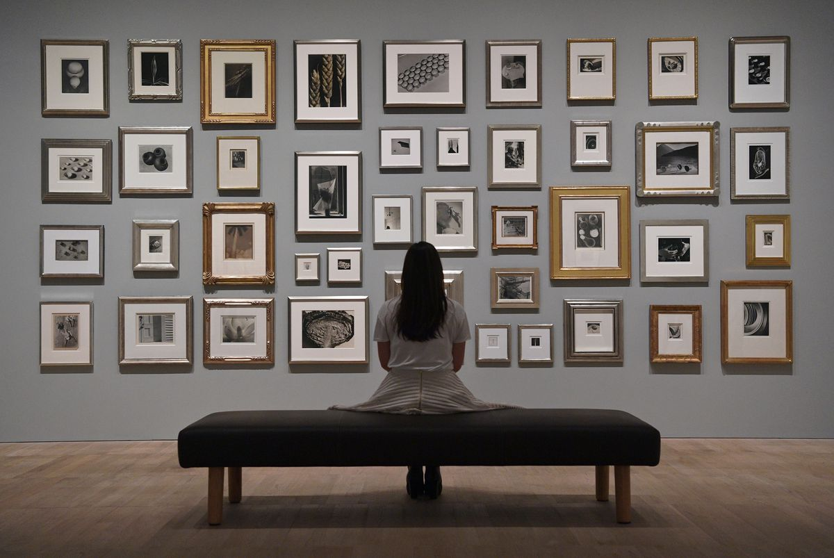 A woman sits on a bench looking at a wall of photographs at the Tate Modern museum in London.