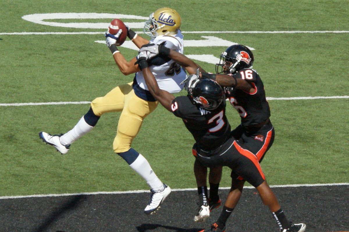 UCLA's Taylor Embree pulls in a touchdown pass despite the efforts of Oregon St.'s Anthony Watkins (3) and Rashaad Reynolds in the Bruins' 27-19 win over the Beavers. (Photo by Andy Wooldridge)