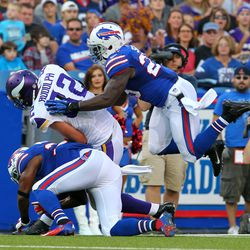 Aug 16, 2013; Orchard Park, NY, USA;  Minnesota Vikings tight end Kyle Rudolph (82) makes a catch while Buffalo Bills strong safety Da'Norris Searcy (25) tries to make a tackle during the first half at Ralph Wilson Stadium.