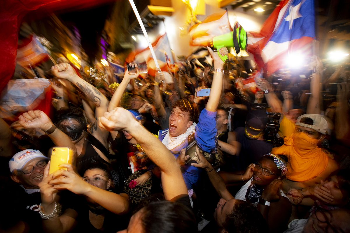 People celebrate on July 24 in San Juan, Puerto Rico, after Gov. Ricardo Rosselló announces that he will resign.