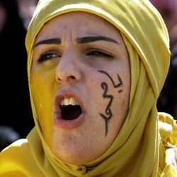 """A Lebanese girl with writing on her face in Arabic that reads: """"oh, Muhammad,"""" as she chants slogans during a demonstration about a film ridiculing Islam's Prophet Muhammad in Lebanon's eastern city of Baalbek, Lebanon, Friday, Sept. 21, 2012. Anger over insults to Islam's Prophet Muhammad isn't enough to bring Lebanon's divided Sunni and Shiite Muslims together. The two sects, which have been locked in sometimes violent political competition, hold separate protests. A hardline Sunni cleric accuses Shiite Hezbollah of using the protests to distract from the fighting in neighboring Syria."""
