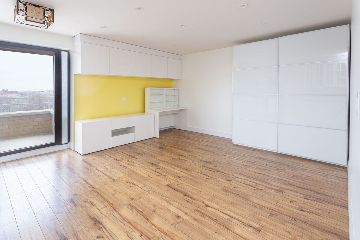 A living room with hardwood floors, a door that leads to a balcony, and white walls with a piece painted yellow.