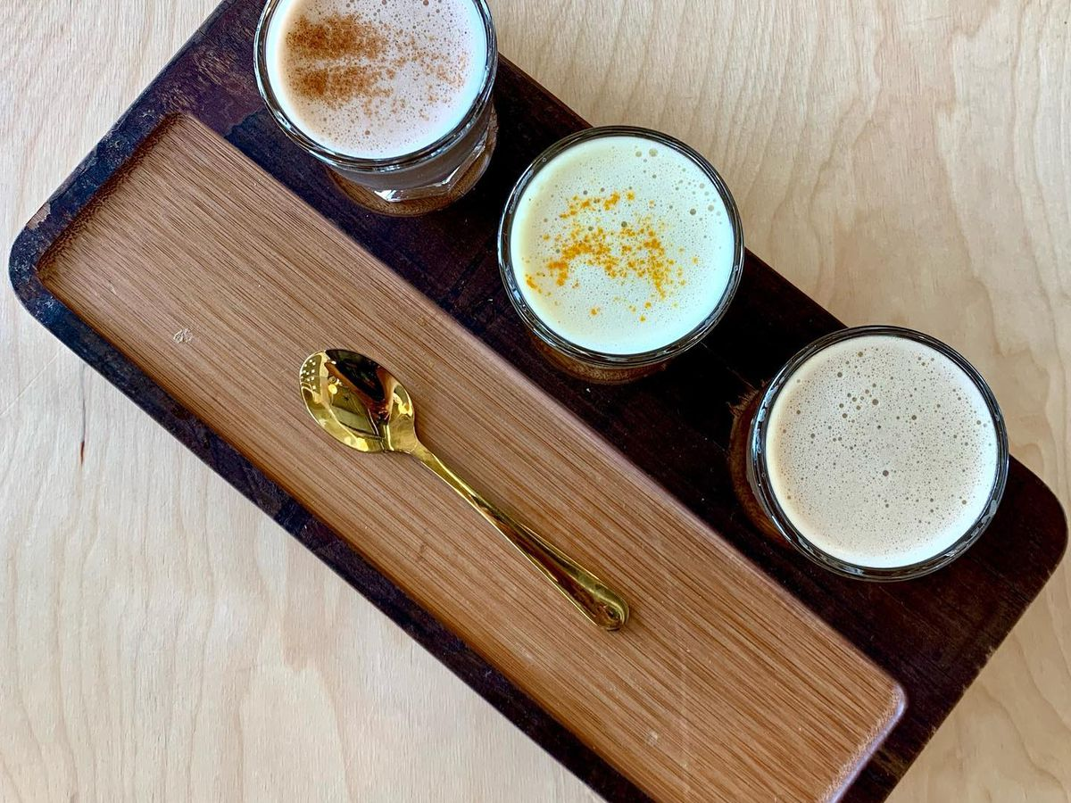 Three chai teas on a tray with a gold spoon.