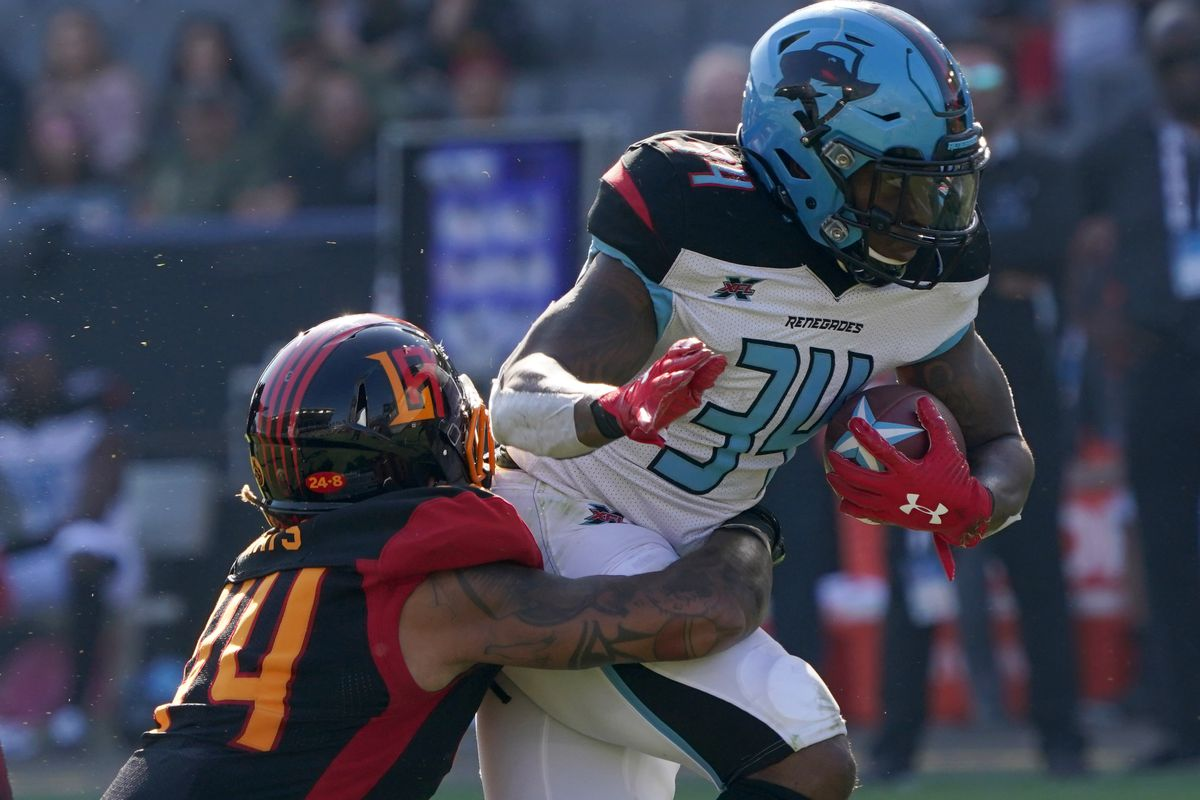 Dallas Renegades running back Cameron Artis-Payne is defended by LA Wildcats linebacker Willie Mays in the fourth quarter at Dignity Health Sports Park. The Renegades defeated the Wildcats 25-18.