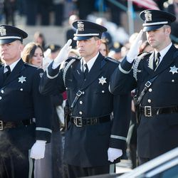 Officers salute as Unified police officer Doug Barney's casket is placed in the hearse following funeral services at the Maverik Center in West Valley City on Monday, Jan. 25, 2016.