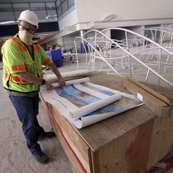 """Jason Scott, Gordon Huether Studio operations manager, unrolls proofs of murals that will hang in the new Salt Lake International Airport in Salt Lake City on Friday, May 22, 2020. Artist Gordon Huether designed""""The Canyon""""installation that will be featured in the airport as well."""