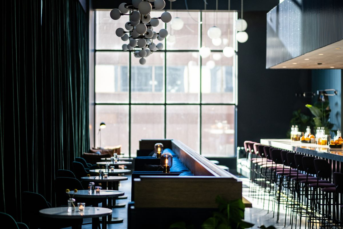 A bar interior features lots of blue tones, a giant window, and a light fixture made up of many white spheres