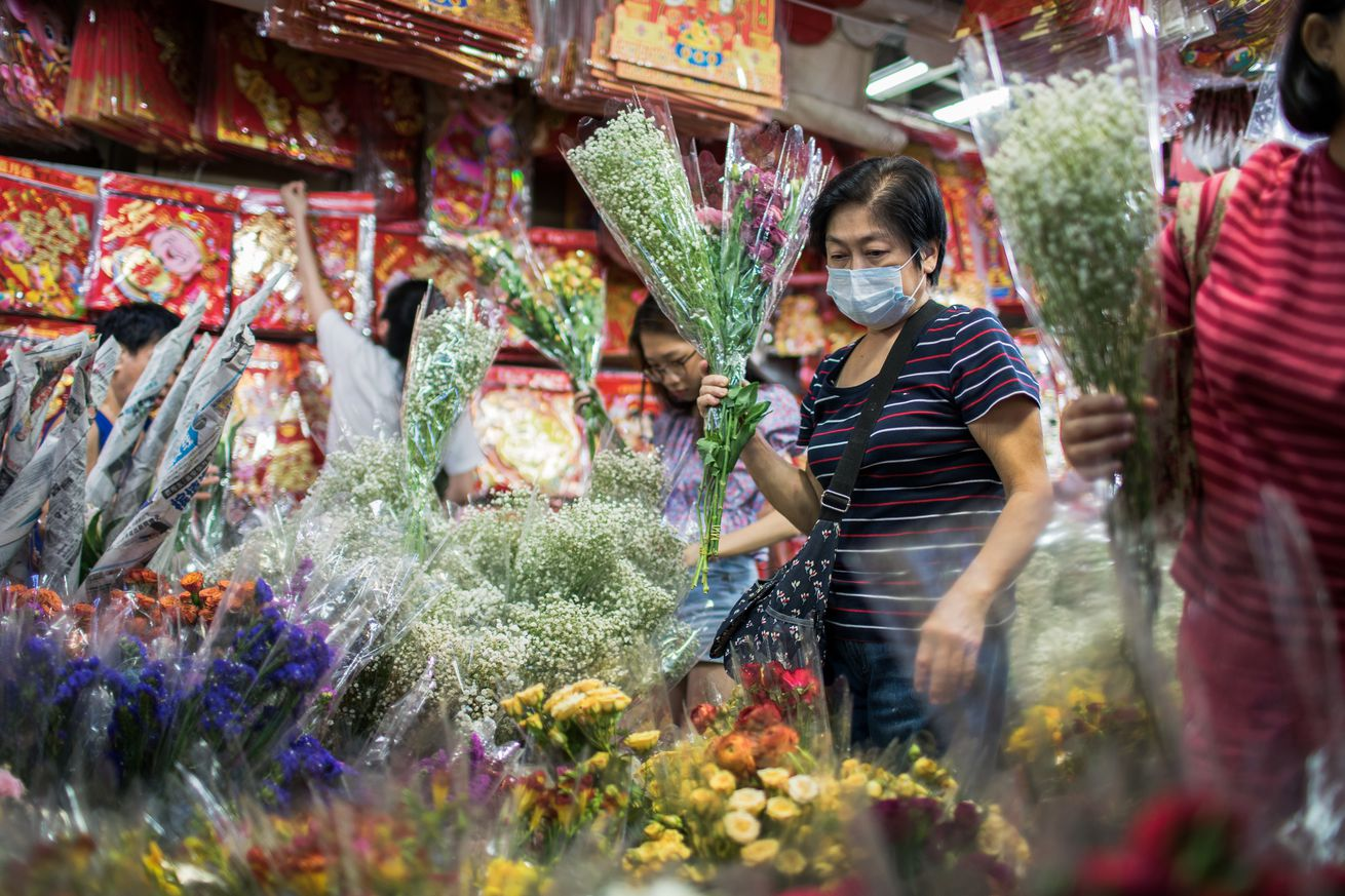 An old woman wears a surgical mask while buying flowers...