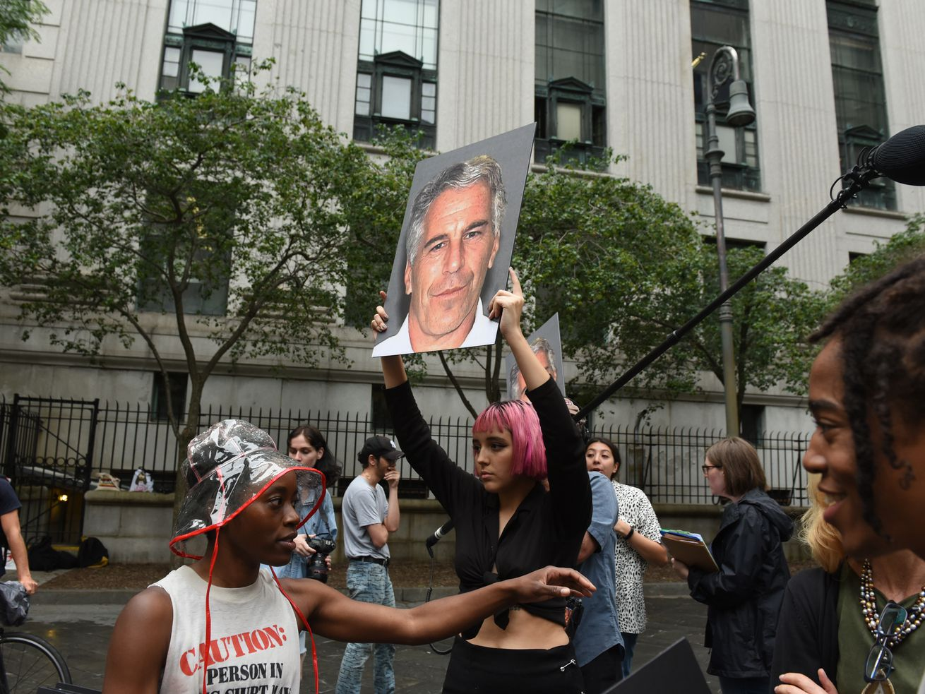 A protest group holds up signs of Jeffrey Epstein in front of a New York City federal courthouse in July 2019, the month before his death.