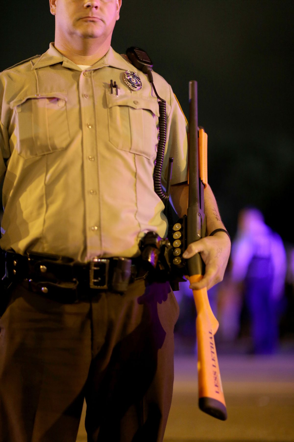 A police officer stands with a shotgun in Ferguson, Missouri.