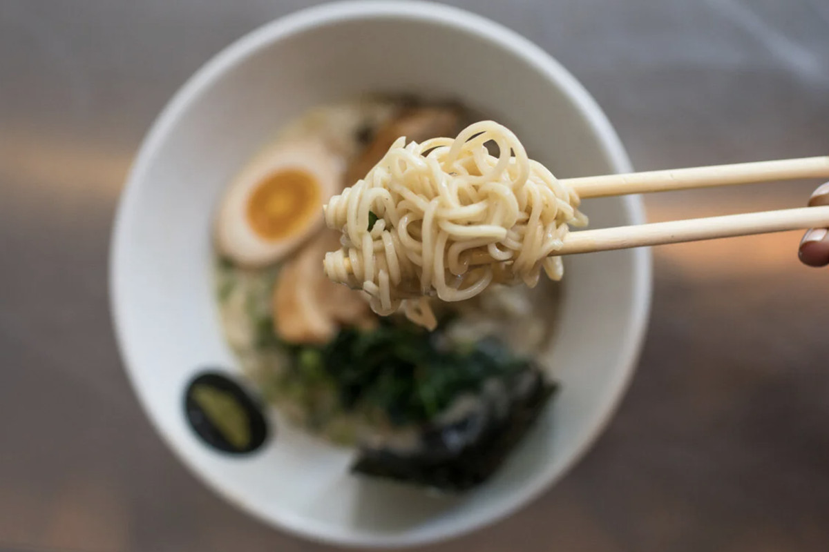 Chopsticks lift a tangle of ramen noodles from a bowl filled with hard-boiled egg, seaweed, and broth; topdown view.
